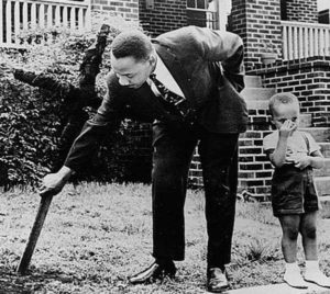 Martin Luther King Jr. retira uma cruz queimada de seu quintal com seu filho em 1960.
