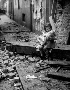 Menina se senta em frente à sua casa em ruínas em Londres, em 1940.