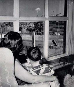 Uma mãe e seu filho olham para a nuvem de cogumelo após um teste nuclear em Las Vegas em 1953.