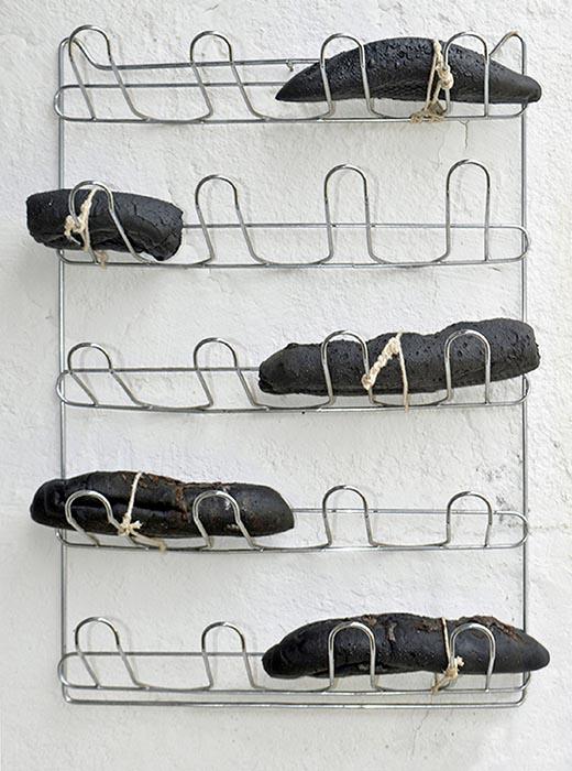 carbopannis ou pao que diabo amassou, 2003 Pães de trigo carbonizados, barbante, cera de abelha, aço inoxidável (54 x 41 x 16 cm)